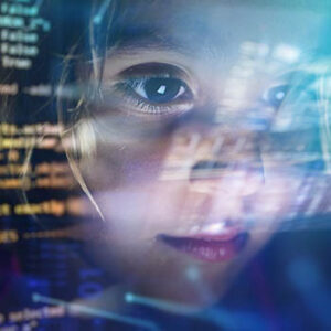 A young girl's face is reflected in a computer screen full of code.